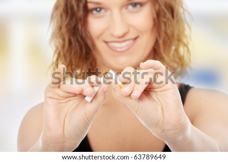 Young woman quiting smoking - focus on hand