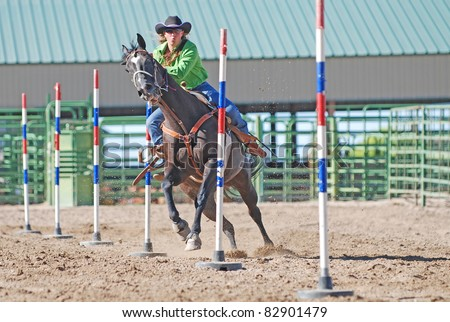 Young woman racing her horse in a rodeo pole bending event.