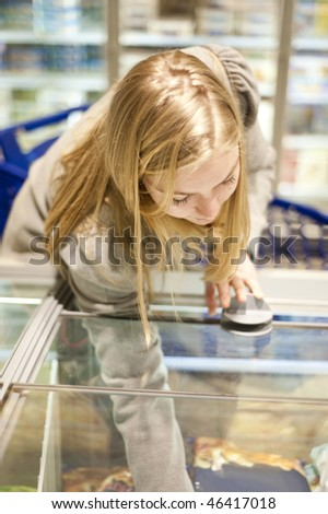 Young woman reaching in a freezer of the frozen food section of a supermarket, shallow Depth of field, focus on the eyelids