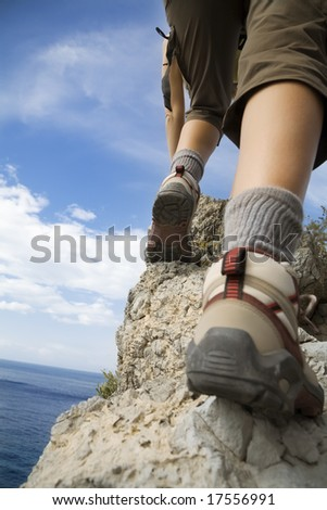 young woman reaching the top of a mountain.