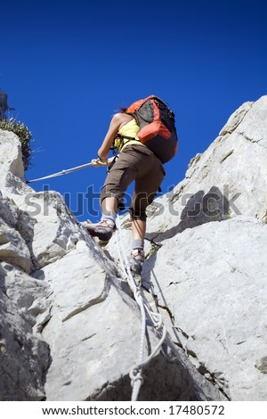 young woman reaching the top of a mountain. Copy space