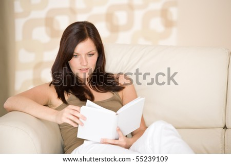 Young woman read book relaxing on sofa in lounge