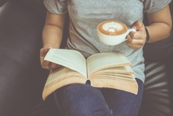 Young woman reading a book and holding cup of coffee