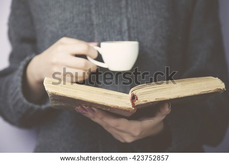 Young woman reading a book and holding cup of coffee #423752857
