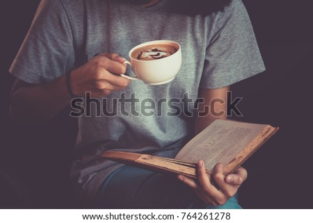 Young woman reading a book and holding cup of coffee #764261278