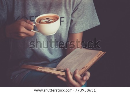 Young woman reading a book and holding cup of coffee #773958631