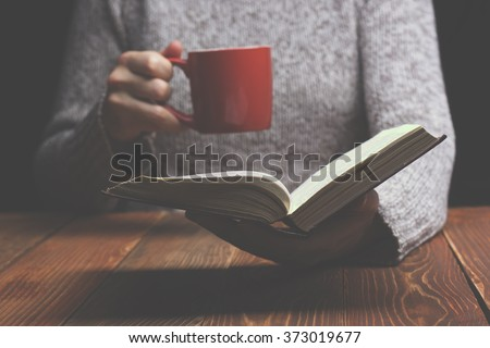 Young woman reading a book and holding cup of tea or coffee. Toned image