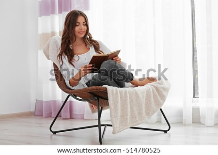 Young woman reading a book and sitting on comfortable chair at home