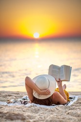 Young woman reading a book at the beach while the sun rise. She's wearing a orange dress and white hat