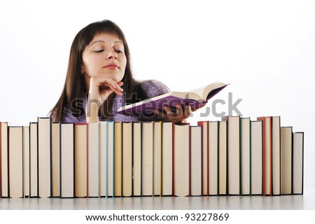 young woman reading a book behind a big pile of books