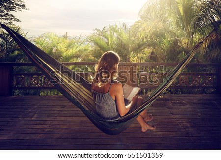 Young woman reading a book in a hammock on the terrace in the jungle at sunset #551501359