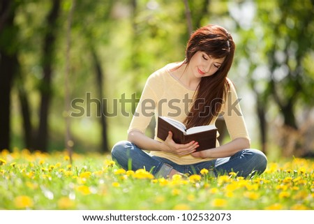 Young woman reading a book in the park with flowers #102532073