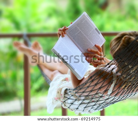 Young woman reading a book lying in hammock - stock photo