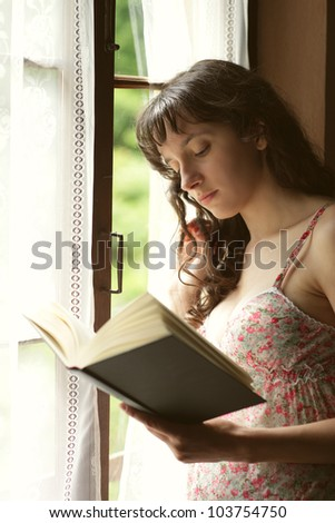 young woman reading a book near a window