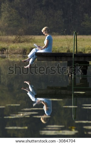 young woman reading a book on a pier by the lake