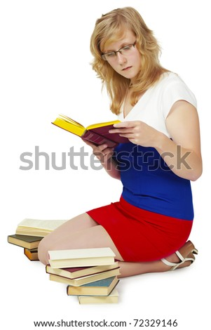 Young woman reading a book sitting on the floor