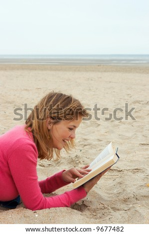 Young woman reading a funny book on the beach