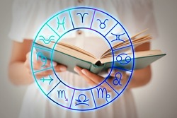 Young woman reading book and illustration of zodiac wheel with astrological signs on light background