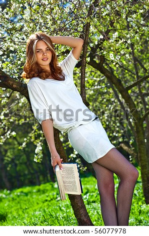 Young woman reading book in summer park.