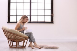 Young woman reading book near window with blinds at home. Space for text