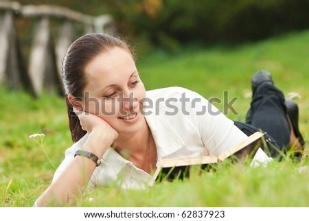 young woman reading book on green field