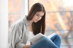 Young woman reading book on windowsill at home
