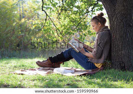 Young woman reading book under the tree during picnic in evening sunlight #159590966