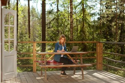 Young woman reading document and working on laptop computer sitting at table on wooden balcony of country house surrounded by pine trees