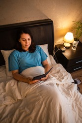 young woman reading electronic book with night light lamp