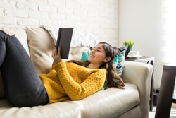 Young woman reading humorous novel while lying on sofa