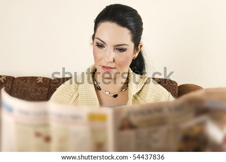 Young woman reading new in her home and sitting on sofa