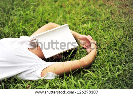 young woman reading on grass