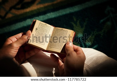 Young woman reading the Koran at the mosque - stock photo
