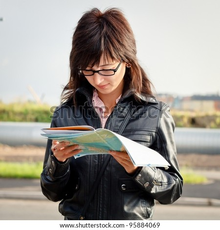 young woman reading tourist map outdoors