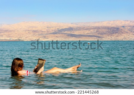 young woman reads a book floating in the waters of the Dead Sea in Israel #221445268