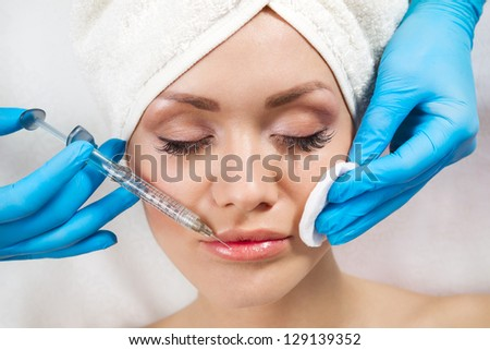 Young woman receiving a botox injection in her lips, close up