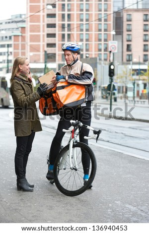 Young woman receiving a package from courier delivery man with bicycle and backpack