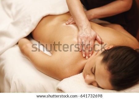 Young woman receiving back massage at spa salon. Professional masseuse working with her client recreation rejuvenation pampering therapy relaxing resort hotel travel exotic procedure treatment joy