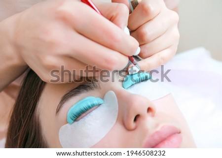 Young woman receiving eyelash lamination procedure in a beauty salon, close up Foto stock ©