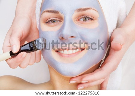 Young woman receiving facial mask at beauty salon