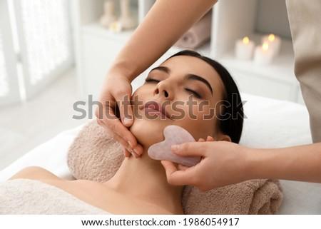 Young woman receiving facial massage with gua sha tool in beauty salon Foto stock ©