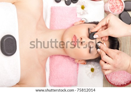 young woman receiving facial massage with mineral stone