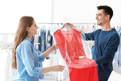 Young woman receiving her dress at dry-cleaner's