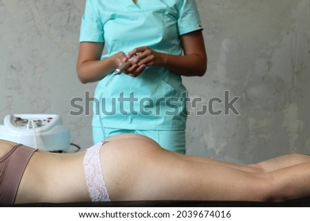 Young woman receiving radio frequency lifting massage. Hardware anti-cellulite massage. RF lifting procedure. The beautician guides the device along the client's leg. Legs anti-cellulite procedures. Stok fotoğraf ©