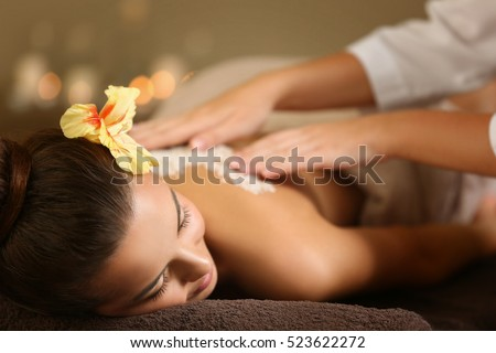 Young woman receiving salt massage in spa salon