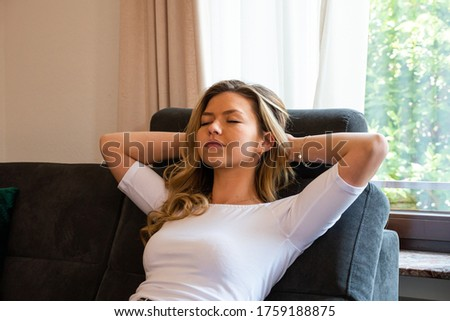 Young woman reclining in sofa recliner. Eyes closed with hands behinds head. Medium shot. Side view.  ストックフォト ©