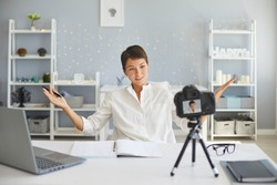 Young woman recording video on camera sitting at desk in cozy home office. Knowledgeable business blogger, social media influencer or female coach sharing experience making pre-recorded webinar