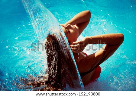 young woman refresh in pool under waterfall, retro colors