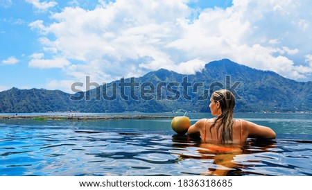 Young woman relax in infinity pool with lake view. Natural hot spring spa under Batur volcano. Travel in Kintamani, Bali. Healthy lifestyle, recreational activity on family summer holiday. Foto stock ©