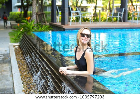 young woman relax in swimming pool, looking at camera wearing sunglassses and enjoy weather in tropical country on background of apartment building on sunny day with sunshine. Concept of enjoying life #1035797203